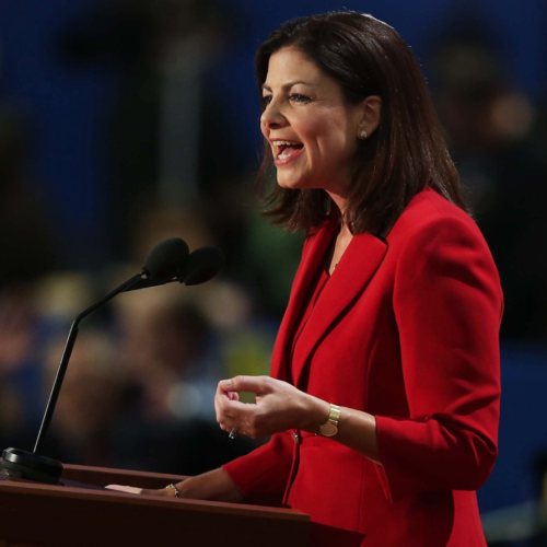 A 3/4 view of a poised speaker, wearing a red suit giving a speech at a lectern. The crowd behind the speaker is blurred and out of focus.