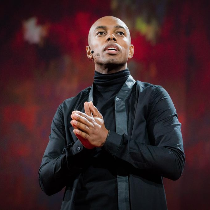 A confident speaker, dressed in black, looking towards the crowd with his hands together, separated visually from a red, textured background via atmospheric perspective.