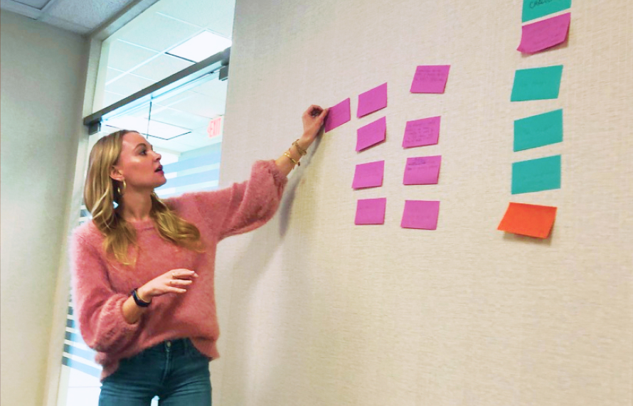 Viget project manager Mellissa Southern organizing and sorting post-its on a large whiteboard during a kickoff